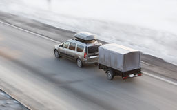 Car with trailer rides on the winter road. Car with a trailer and an upper trunk goes through the winter road royalty free stock images