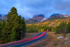 Car Trails Going up a Mountain Road during a stormy cloudy morning. Car Trails Going up Bear Lake road in Rocky Mountain National Park right before sunrise on a stock photo