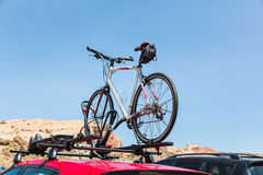 Car is transporting bicycle on the roof. Stock Photo
