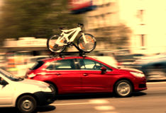 Car transporting bike. Bikes on the roof of a red car that transports it on its roof by the street in a city stock photos