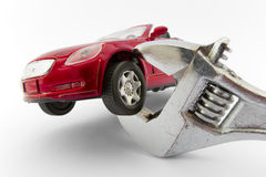 Car trapped by monkey wrench. A toy car being held by a monkey wrench (which appears giant relative to the size of the toy car royalty free stock images