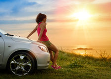 Car travel and freedom. Female driver enjoying freedom and beautiful sunshine over the sea after driving to coast in summer vacation travel. Woman relaxing and