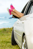 Car travel freedom and relax. Car travel vacation and relax concept. Woman legs out the windows enjoying freedom and relaxing on nature coast landscape Royalty Free Stock Photo