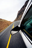 Car travel through mountains. Focus on mirror and motion blur on road Stock Photos