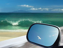 Car traveling to paradice beach. Drive as fly. Car is moving in-front of the tropical beach. There are beautiful sea wave of paradise beach, road, sky on the Royalty Free Stock Image