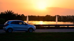 Car travelling on highway. This is a picture showcasing the journey of the traveller in the car, he drives on the highway as the sun sets down and besides there Royalty Free Stock Images
