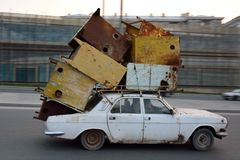 Car travelling overloaded with scrap on roof in Baku, Azerbaijan Stock Images