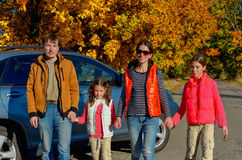 Car trip on autumn family vacation. Happy parents and kids travel and have fun, car insurance concept Royalty Free Stock Images