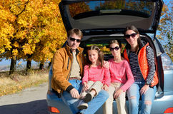 Car trip on autumn family vacation. Happy parents and kids travel and have fun, car insurance concept Royalty Free Stock Photography