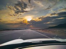Car trip on highway. Car driving on the highway with epic sunset. Road view from inside car behind console. First-person photo. travel background royalty free stock photography