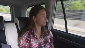 Car trip. Woman looks on alpine landscape. Pensive woman sits on a backseat of car looking out of window to beautiful green summer landscape stock video footage