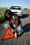 Car trouble. A woman putting a warning triangle in front of her car, country dust y road, white car in the background Stock Images