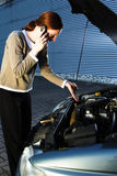 Car Trouble. A young female driver having car troubles and talking on the phone with the road help service Stock Photography