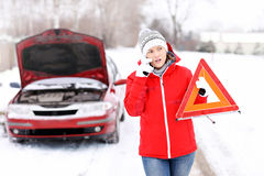 Car trouble. A picture of a young woman having a problem with a car on a winter road Stock Photo