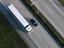 Car and truck. A car and a truck driving next to each other on a highway . air view Royalty Free Stock Photography
