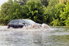 Car trying to drive against flood on the street in Gdansk, Poland. Royalty Free Stock Photos