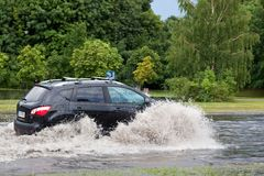 Car trying to drive against flood on the street in Gdansk, Poland. Stock Photography