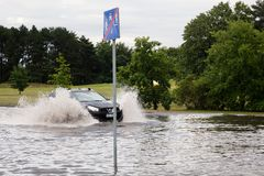 Car trying to drive against flood on the street in Gdansk, Poland. Stock Photo