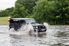 Car trying to drive against flood on the street in Gdansk, Poland. Stock Photos