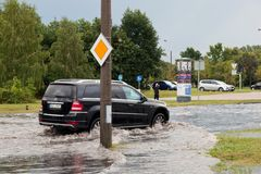 Car trying to drive against flood on the street in Gdansk, Poland. Royalty Free Stock Photo