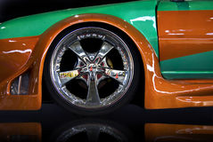 Car tuning. Orange and green tuning car, isolated over black mirror Royalty Free Stock Photo