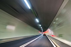 Car in tunnel. Driving through a tunnel in Switzerland. The lights of the cars infront gave a nice touch of color to it Stock Photo