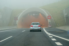 Car before tunnel on foggy road Stock Photos