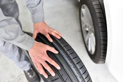 Car tyre change in a workshop. Hand rolls tire stock photography