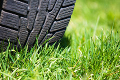 Car tyre on the green grass Stock Images