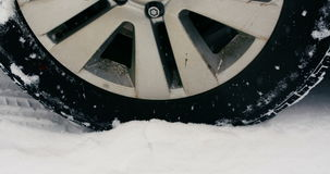 Car tyre moving on snow during snowfall stock video footage