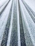 Car tyre tracks on a frozen ice tarmac road. Frozen water turns into ice on a tarmac road over which cars have driven leaving behind fresh tyre tracks in the Stock Image