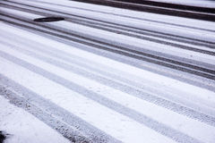 Car tyre tracks on snowy road. Winter road covered first snow and car tyre tracks background Stock Photography