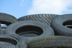 Car Tyres in Recycle Pile against Blue Sky stock image