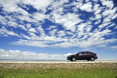 Car under the blue sky. A red car is parking under the blue sky with white clouds Stock Photo