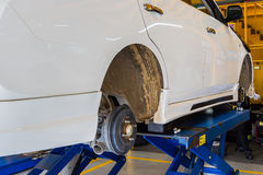 Car under repair on hoist at service station. Stock Photo