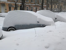 Car under snow, Natural disasters winter, blizzard, heavy snow paralyzed the city, collapse. Snow covered the cyclone Europe. Stock Photos