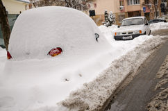 Car under snow. A parked car is covered and stuck in snow. on a street of Craiova, city of Romania, Europe, January 27th royalty free stock photo