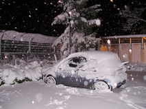 Car under a snow in parking lot. Snow falls Royalty Free Stock Photos