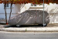 Car under textile cover outside. Stock Photo