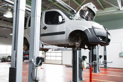 Car undergoing service in garage raised on lift. Front view on gray car without wheels raised on lift in garage with open hood. Auto service industry concept royalty free stock photo