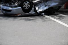 Car Upside-Down. A silver car after and accident. Upside-down with broken glass and pieces on the street stock image
