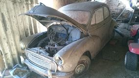 A rusty old barn find classic car. Car vehicle bumper bonnet morris minor flat tyre engine bonnet up popped mud dirt windscreen inside cobwebs red leather stock photography