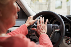 In car view of senior female driver using the horn in a car Stock Images