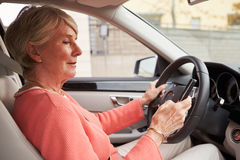In car view of senior female driver using smartphone Royalty Free Stock Photography