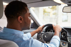 In car view of young male African American driver with coffee Stock Image