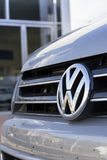 Car with Volkswagen logo in front of dealership building Stock Photos
