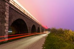 Car vs Train. The bright trace of a car below, and of a train one above a 16-bridges structure during a foggy and violet sunset stock photos