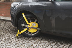 Car was locked with yellow clamped vehicle, wheel lock. Parking on forbidden place Royalty Free Stock Images
