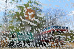 Car Wash. Soapy suds cover a car windshield on a sunny day Stock Photos