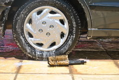 Car wash. Ing showing the car's back tire with a brush Royalty Free Stock Photos